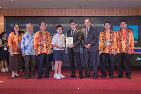 教育部副部长张盛闻上议员颁发奖杯予全国华小华语演讲比赛冠军得主赖俊益同学。