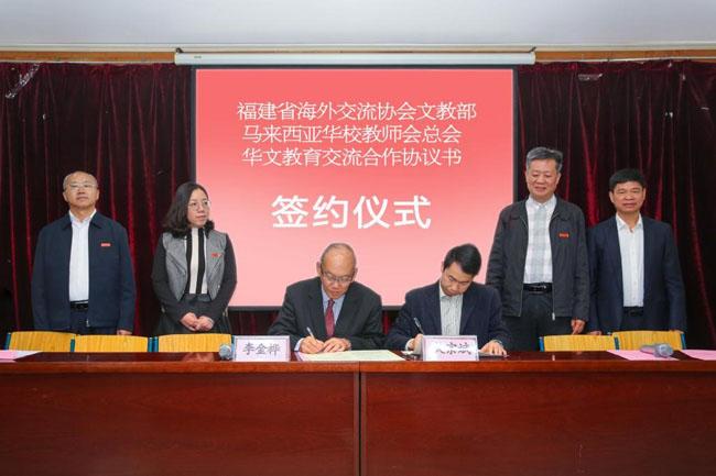 李金桦(左三)与福建省海外华文教育发展中心副主任吴宗斌(右三)签署华文教育交流合作协议书。