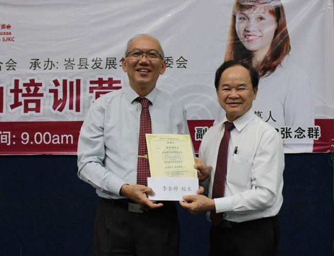 柔佛州董教联合会/董总主席陈大锦(右)赠送感谢状予李金桦。